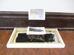 Détail de l'installation (cadre, toile, brique, terre, impressions numériques)